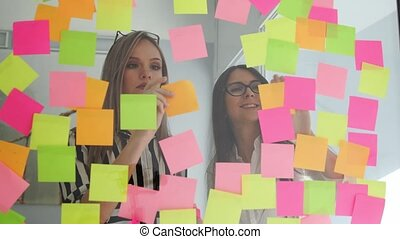 Creative business team brainstorming ideas working together sharing data late at night after hours in modern glass office. Two very beautiful girls in office clothes blonde and brunette with glasses look at the colored stickers and offer ideas