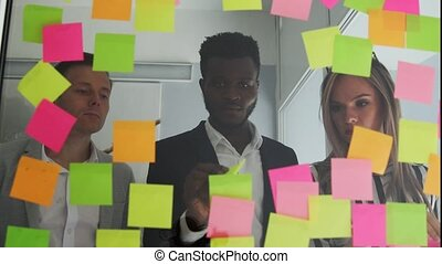 Creative business team brainstorming ideas working together sharing data late at night after hours in modern glass office. Multi ethnic creative team conducts brainstorming all their ideas are pasted on colored stickers on the glass wall. African American male and blonde team up in the office