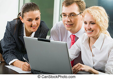 Creative business team gathered together around the laptop...
