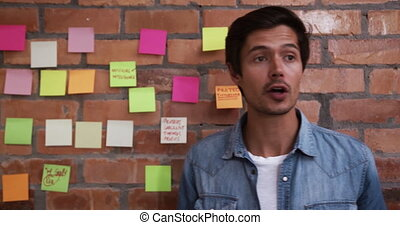 Caucasian professional businessman working in a modern office, talking and pointing to memo notes on brick wall. Business creativity technology.