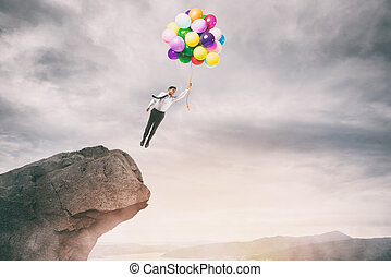 Creative businessman holding colorful balloons flies from the peak of a mountain