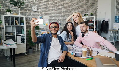 Creative businessman taking selfie with business team in modern office