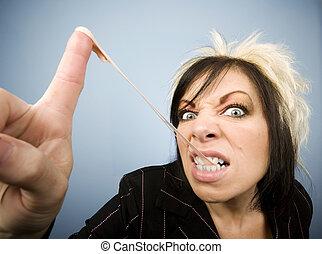 Portrait of a creative businesswoman stretching gum, on her fingertip