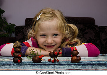 creative child with home made autumn craft