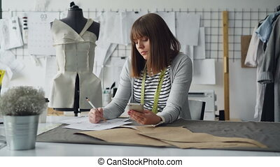 Creative clothing designer is looking at smartphone and...