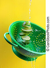 Creative concept with levitated lime in green colander on a bright yellow background
