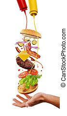 Creative cooking of hamburger. Flying ingredients, mustard and ketchup splashes