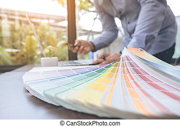 Creative creativity graphic designer working with graphics tablet,laptop and smart phone, colour chart at workplace on wooden desk , colour ideas style concept