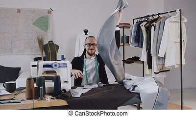Creative designer and tailor is sitting at the desk in his...