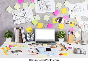 Creative designer desktop with blank white laptop, other gadgets, financial reports, construction sketches, numerous colorful supplies, stickers and other items. Mock up. Modern workspace concept