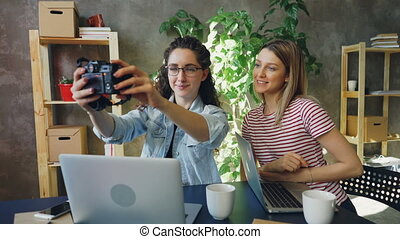 Creative designers are posing for selfie together sitting in modern office. They are using camera, laughing and socialising. Youth lifestyle concept.