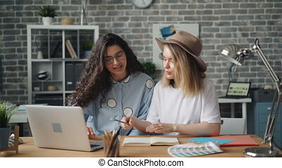 Creative designers writing in notebook then working with laptop in office