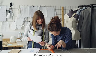 Creative dressmakers are using smartphone and looking at...