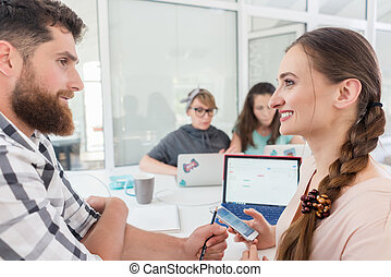 Creative female freelancer smiling to co-worker
