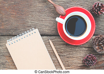 Creative flat lay cup of coffee with craft paper diary on wooden table