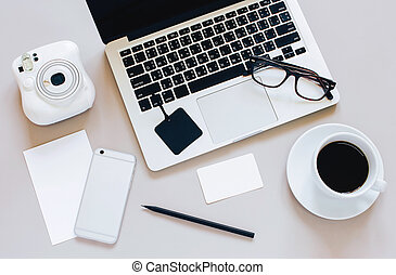 Creative flat lay photo of workspace desk with laptop, blank paper, coffee, eyeglasses, smartphone and camera on grey background