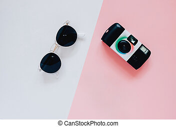 Creative flat lay style in fashion concept with camera and sunglasses on minimal color background, top view