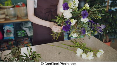 Creative florist making beautiful bouquet holding bunch of...