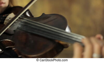 Creative girl in black dress playing the violin on vintage background