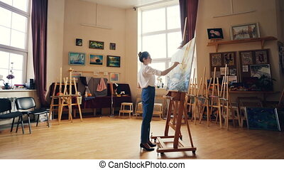 Creative girl is focused on painting picture marine...