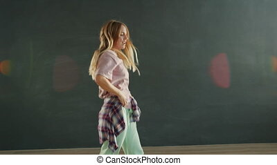 Creative girl with long blond hair is dancing in modern dance studio in dark room having fun enjoying hip-hop show. People and contemporary art concept.