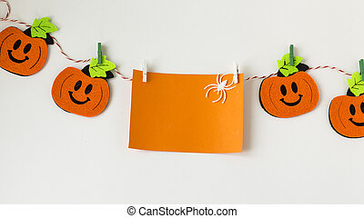 Creative Halloween Day composition flat lay top view holiday celebration orange pumpkins, white card with place for text on the rope on white paper background copy space