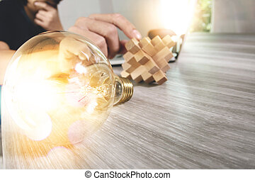 creative hand showing wood puzzle and light bulb with laptop computer and tablet computer as design concept