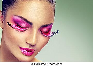 Creative holiday makeup with false long purple eyelashes...