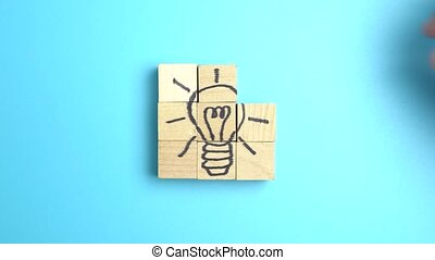 Hand puting together wood blocks to form a lightbulb picture for creativity, innovation or idea conceptual