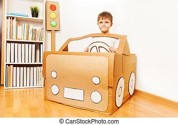 Creative kid boy plays with his cardboard car