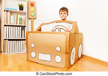 Creative kid boy plays with his cardboard car
