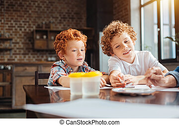 Creative kids painting with watercolors in kitchen