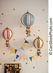 Creative lamps in form as air balloons on white wall in playroom interior