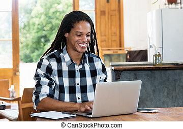 Creative latin american man with dreadlocks at computer -...