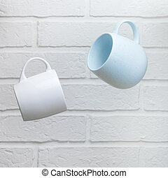 Creative levitation of two blue and white cups against the background of a kitchen stone brick wall of a milky shade, the concept of clean dishes