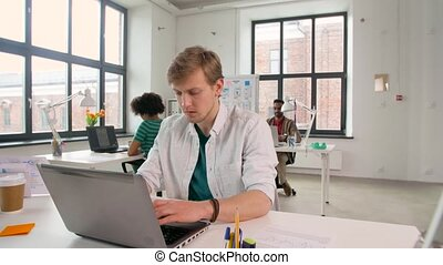 creative male office worker typing on laptop - business and...