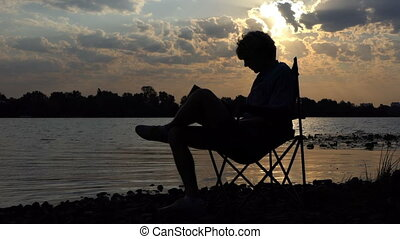 Creative Man Sits And Writes in His Notepad Smth on a Nice Riverbank