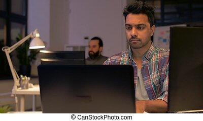 creative man with laptop working at night office