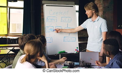 Creative manager is using whiteboard at business meeting pointing at chart and talking while group of people is listening and learning new information.
