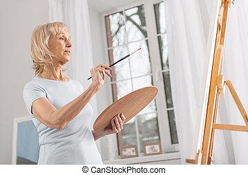 Creative mature woman estimating drawing