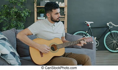 Creative Middle Eastern guy playing guitar at home enjoying musical instrument