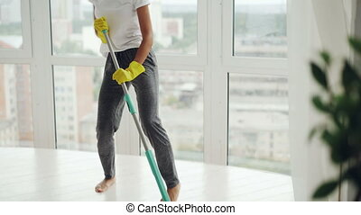 Creative mixed race woman is listening to music in headphones, dancing and singing during clean-up at home, girl is washing floor and having fun enjoying routine work.