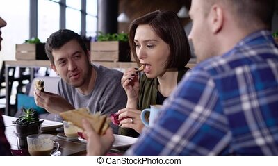 Creative modernly dressed friends met at lunch time during the break. Girls and boys left the office to eat on a sandwich and drink coffee. Friends communicate on various topics in your favorite cafe.