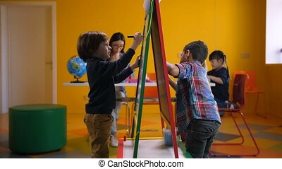 Creative multicultural boys drawing on easel board -...