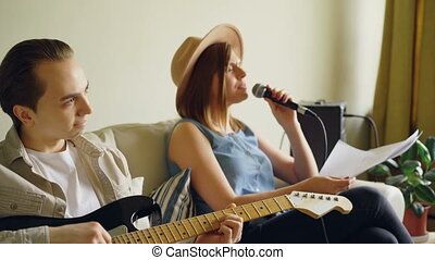 Creative musical duet is practising at home woman is singing...
