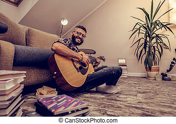 Cheerful happy man sitting with his guitar