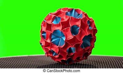 Creative origami ball on green screen. Flowery kusudama ball...