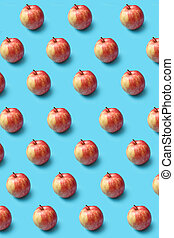 Creative pattern from fresh organic red apples on a blue background.