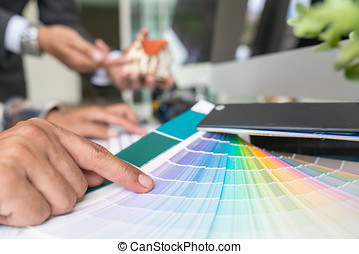 Creative people workplace. Close-up view of hands of young designer woman working with color palette at office desk. Attractive model choosing color samples for design project. Interior shot