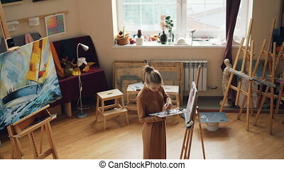 Creative person is painting in art studio using oil paints...